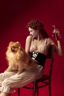 Mittelalterliche junge frau, die saft trinkt und kleinen hund hält