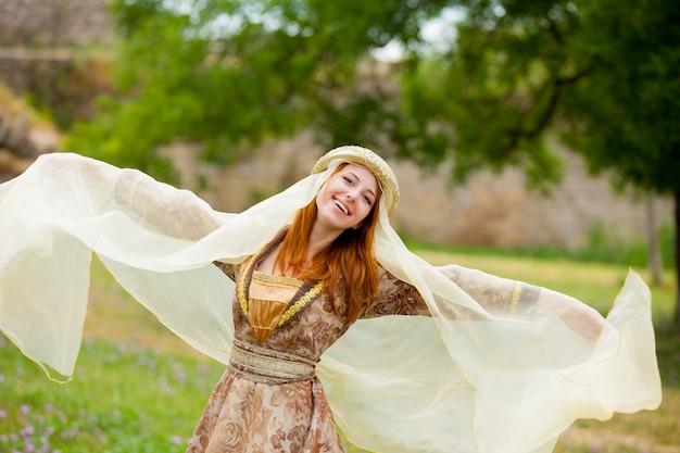 Mittelalterliche junge rothaarige frau in der traditionellen kleidung am coutryside im freien.