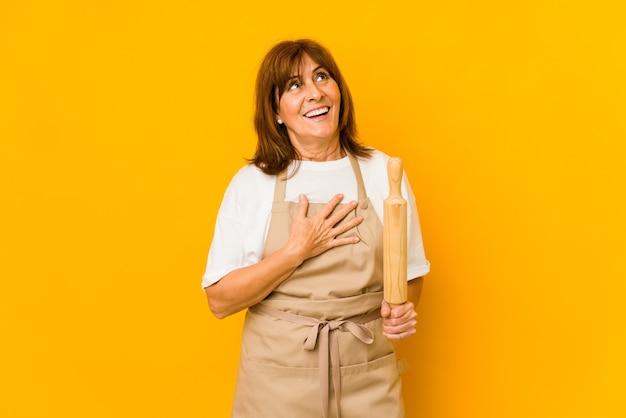 Mittelalterliche köchin, die eine walze isoliert hält, lacht laut und hält die hand auf der brust
