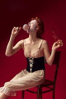 Mittelalterliche rothaarige junge frau als herzogin im schwarzen korsett, in der sonnenbrille und in der nachtkleidung, die auf einem stuhl auf roter wand mit einer süßigkeit sitzen. konzept des vergleichs von epochen, moderne und renaissance.