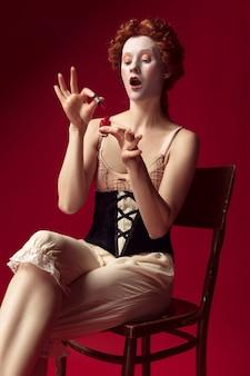 Mittelalterliche rothaarige junge frau als herzogin im schwarzen korsett und in der nachtkleidung, die auf dem stuhl auf rotem raum sitzt