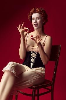 Mittelalterliche rothaarige junge frau als herzogin im schwarzen korsett und in der nachtkleidung, die auf dem stuhl auf roter wand sitzt. mit fingernagelpolitur. konzept des vergleichs von epochen, moderne und renaissance.