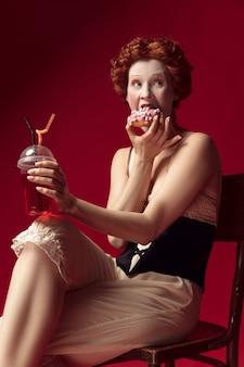 Mittelalterliche rothaarige junge frau als herzogin im schwarzen korsett und in der nachtwäsche, die auf einem stuhl auf rotem raum mit einem getränk und donut sitzt