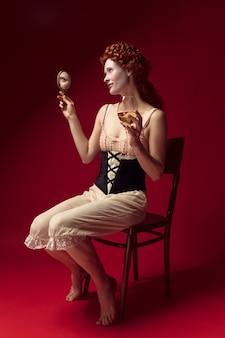 Mittelalterliche rothaarige junge frau als herzogin im schwarzen korsett und in der nachtwäsche, die auf rotem raum mit einem spiegel und einem glas wein sitzen