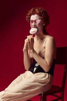 Mittelalterliche rothaarige junge frau als herzogin in schwarzem korsett, sonnenbrille und nachtwäsche sitzen auf einem stuhl auf rotem raum mit einer süßigkeit
