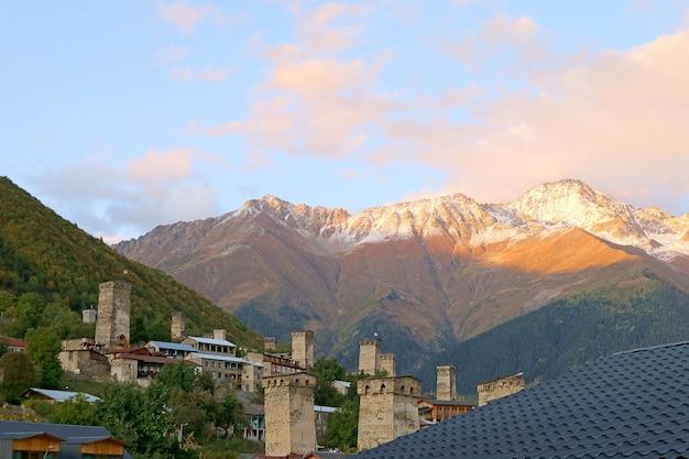 Mittelalterliche svan-turmhäuser mit dem schneebedeckten kaukasus, mestia town, georgia
