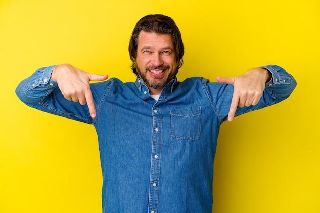 Mittelalterlicher kaukasischer mann lokalisiert auf gelbem hintergrund zeigt mit den fingern nach unten, positives gefühl.