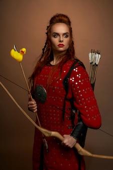 Mittelalterlicher krieger, der pfeil und bogen mit gummiente hält.