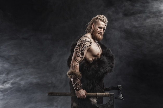 Mittelalterlicher krieger wikinger mit tätowierung und axt