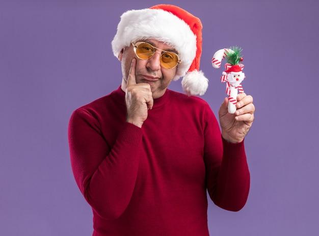 Mittelalterlicher mann, der weihnachtsweihnachtsmütze in gelben gläsern hält, die weihnachtszuckerstange betrachten kamera mit skeptischem ausdruck stehen über lila hintergrund
