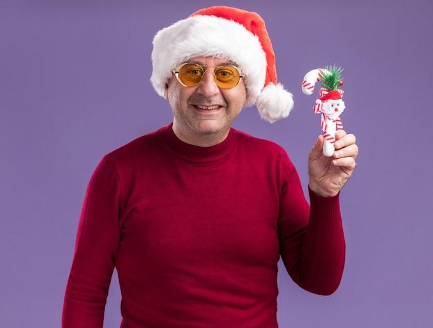 Mittelalterlicher mann, der weihnachtsweihnachtsmütze in gelben gläsern zeigt, die weihnachtsspielzeug betrachten kamera mit lächeln auf gesicht stehen über lila hintergrund