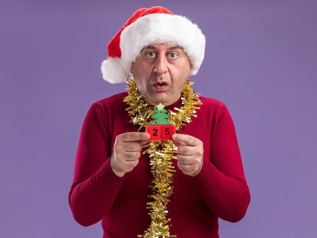 Mittelalterlicher mann, der weihnachtsweihnachtsmütze mit lametta um den hals hält, der spielzeugwürfel mit datum fünfundzwanzig betrachtet kamera besorgt und verwirrt steht über lila hintergrund Kostenlose Fotos