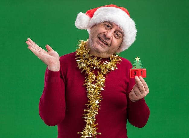 Mittelalterlicher mann, der weihnachtsweihnachtsmütze mit lametta um den hals hält, der spielzeugwürfel mit neujahrsdatum betrachtet und kamera betrachtet, die mit glücklichem gesicht hebt arm über grünem hintergrund steht