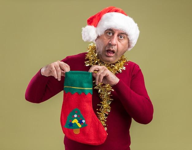 Mittelalterlicher mann, der weihnachtsweihnachtsmütze mit lametta um den hals hält, der weihnachtsstrumpf hält, der kamera überrascht und erstaunt über grünem hintergrund steht