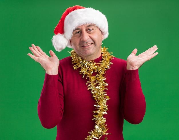 Mittelalterlicher mann, der weihnachtsweihnachtsmütze mit lametta um den hals trägt, der mit glücklichem gesicht mit erhobenen armen lächelt