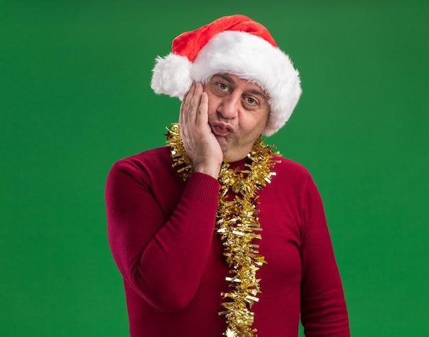 Mittelalterlicher mann, der weihnachtsweihnachtsmütze mit lametta um den hals trägt und kamera mit glücklichem gesicht über grünem hintergrund steht