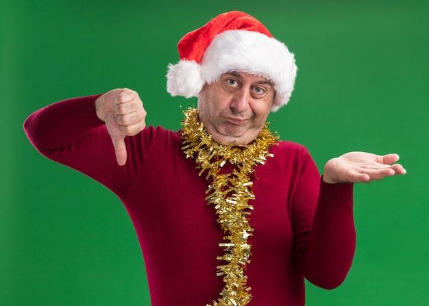 Mittelalterlicher mann, der weihnachtsweihnachtsmütze mit lametta um den hals trägt, verwirrt zeigt daumen hoch und runter