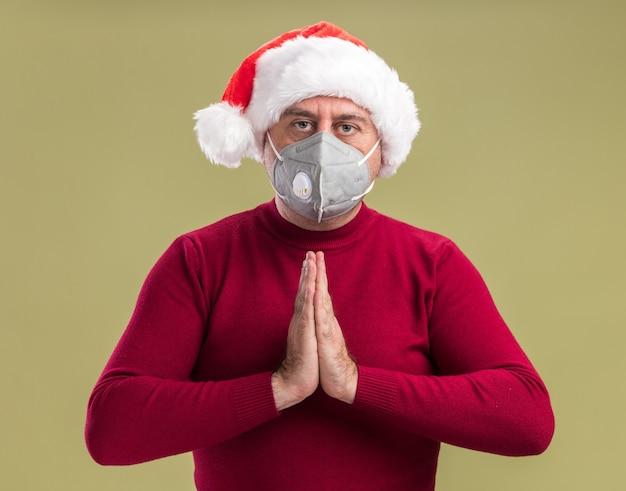 Mittelalterlicher mann, der weihnachtsweihnachtsmütze trägt, die die gesichtsschutzmaske hält, die hände zusammenhält, wie betend mit ernstem gesicht, das über grünem hintergrund steht