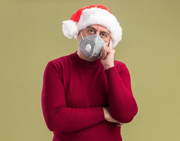 Mittelalterlicher mann, der weihnachtsweihnachtsmütze trägt, die gesichtsschutzmaske betrachtet kamera mit ernstem gesicht, das über grünem hintergrund steht