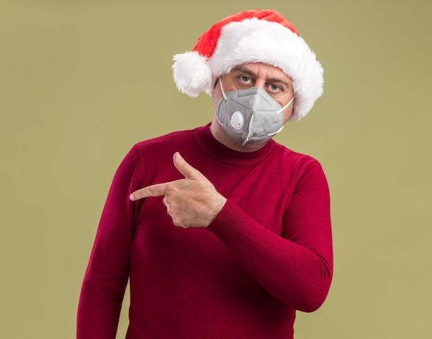 Mittelalterlicher mann, der weihnachtsweihnachtsmütze trägt, die gesichtsschutzmaske trägt, die kamera mit ernstem gesicht betrachtet, das mit zeigefinger auf die seite zeigt, die über grünem hintergrund steht