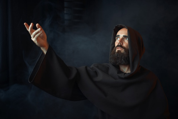 Mittelalterlicher mönch, der gegen ein fenster mit licht betet