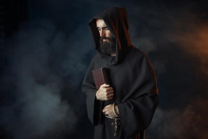 Mittelalterlicher Mönch in Robe hält Zauberbuch in Händen