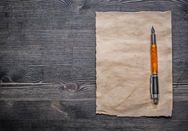 Mittelalterlicher pergamentfüllfederhalter auf holzbrettoberansicht