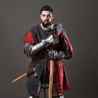 Mittelalterlicher ritter auf grau. porträt des groben schmutzigen gesichtskriegers mit roter und schwarzer kleidung der kettenhemdrüstung und kampfaxt