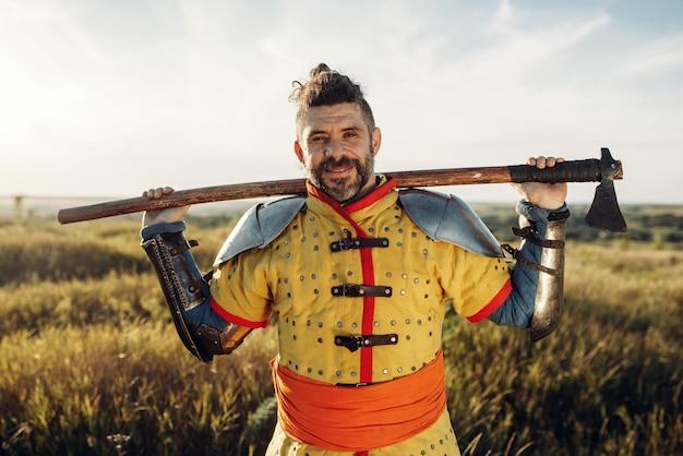 Mittelalterlicher ritter mit axt posiert in rüstung gegenüber der burg, großer kampf. gepanzerte alte krieger in rüstung, die auf dem feld aufwirft