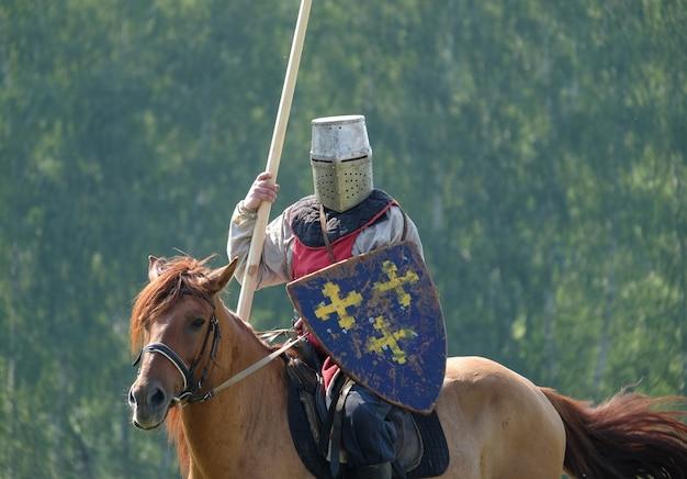 Mittelalterlicher ritter mit einem speer, der ein pferd auf einem hintergrund des grünen waldes im feld reitet. historischer wiederaufbau
