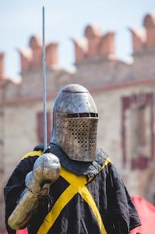 Mittelalterlicher ritter mit schwert in der hand über festung