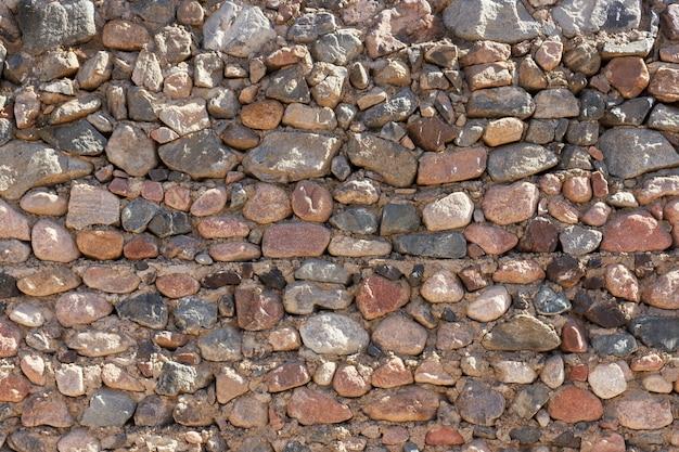 Mittelalterlicher steinwandhintergrund am sonnigen tag. textur