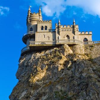 Mittelalterliches schloss gegen blauen himmel mit wolken. schwalbennest