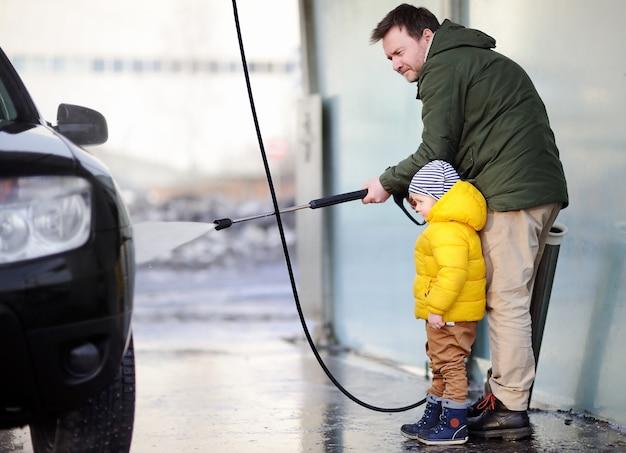 Mittelaltermann und sein kleiner sohn, die ein auto auf einer autowäsche waschen. familienzeit