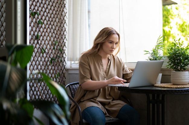 Mittelgroße frau, die am laptop am tisch arbeitet