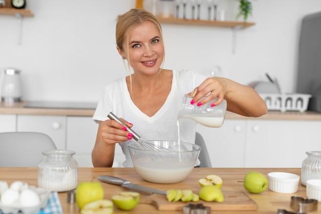 Mittelgroße frau, die mit milch kocht
