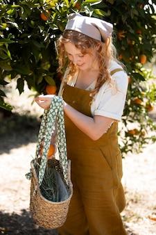 Mittelgroße frau, die orangen pflückt