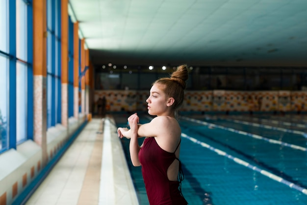 Mittelgroße frau im badeanzug, die sich streckt