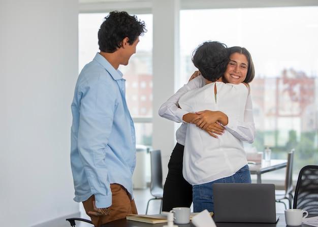 Mittelgroße frauen, die sich bei der arbeit umarmen