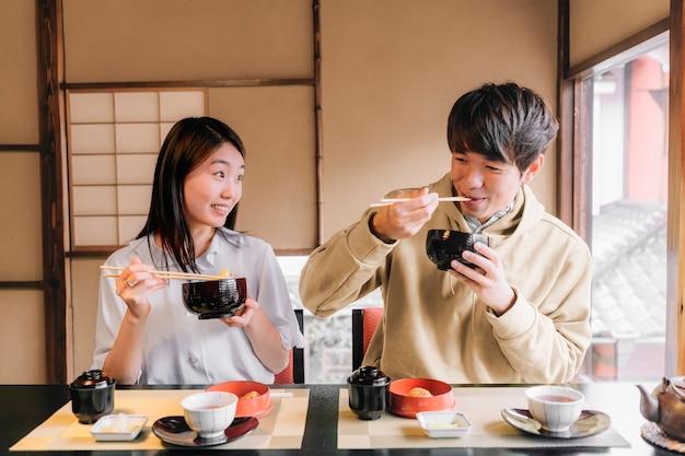 Mittelgroße freunde, die leckeres essen essen eating Premium Fotos