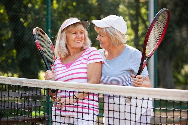 Mittelgroße freunde, die tennis spielen