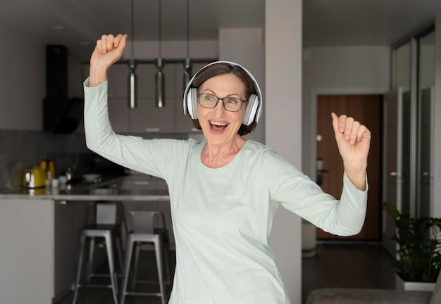 Mittelgroße glückliche frau mit kopfhörern
