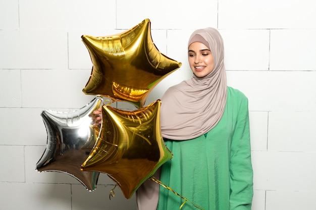 Mittelgroße glückliche frau mit luftballons
