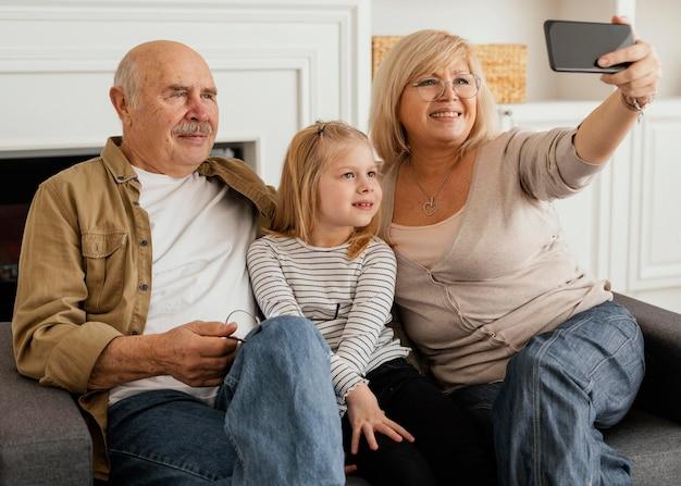 Mittelgroße großeltern und kind, die selfie nehmen