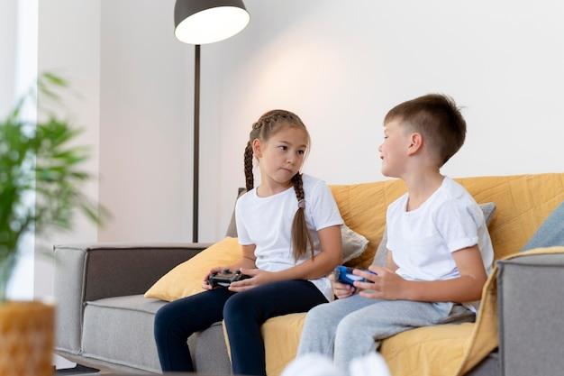 Mittelgroße kinder, die auf der couch spielen