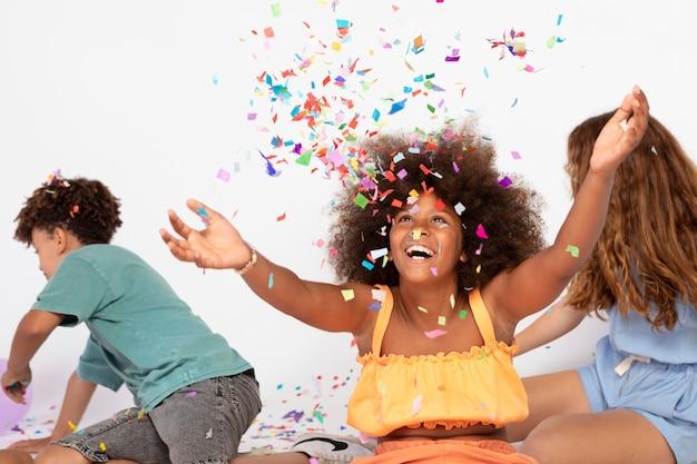 Mittelgroße kinder, die mit konfetti spielen