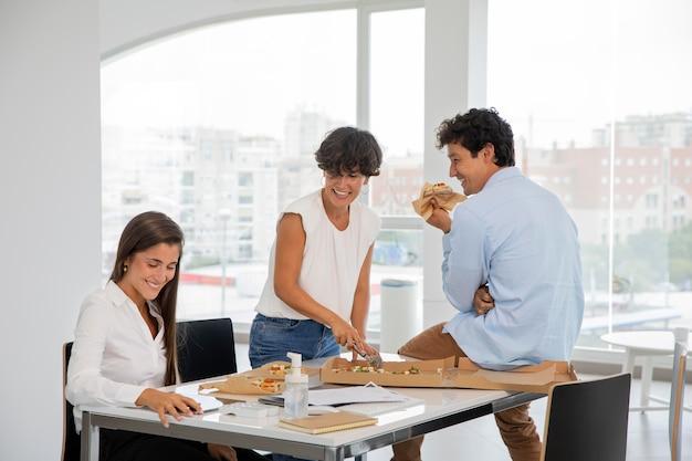 Mittelgroße leute, die bei der arbeit pizza essen