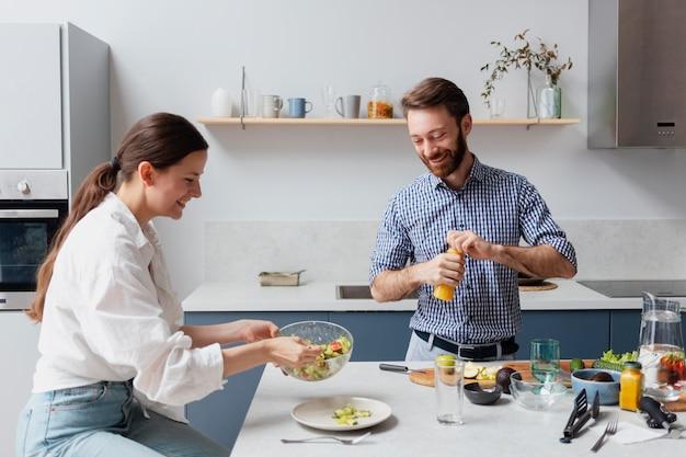 Mittelgroße leute, die essen in der küche zubereiten