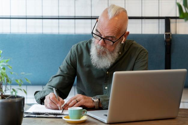 Mittelgroßer älterer mann, der notizen macht