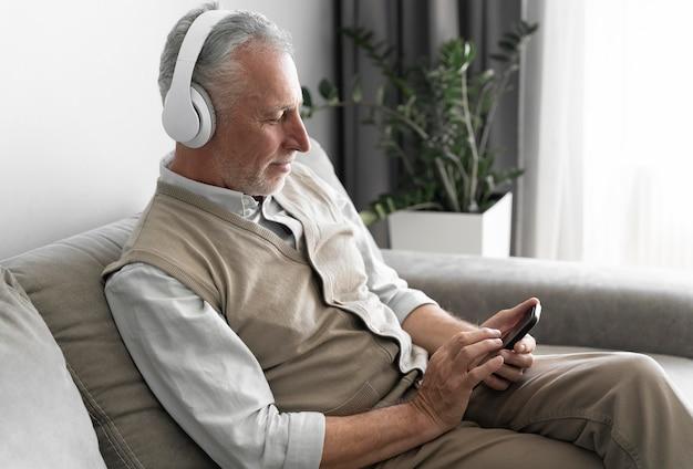 Mittelgroßer älterer mann mit kopfhörern